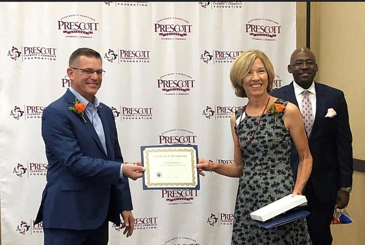 Prescott Mayor Greg Mengarelli congratulates Prescott Unified Director of Instructional Support Kelli Bradstreet, selected by the Prescott Chamber of Commerce for its Educator of the Year award. In the background is Findlay Toyota Center General Manager Jamaal McCoy. Findlay sponsored the event. (PUSD/Courtesy)