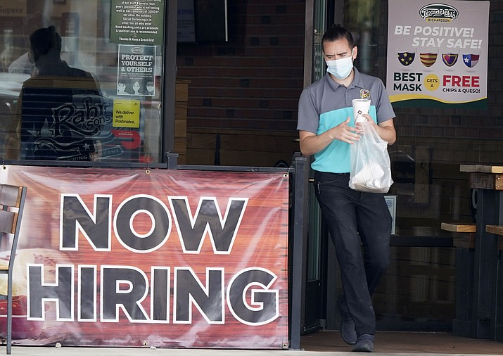 In this Sept. 2, 2020 file photo, a customer wears a face mask as they carry their order past a now hiring sign at an eatery in Richardson, Texas. The number of Americans seeking unemployment benefits fell last week to 751,000, the lowest since March, but it's still historically high and indicates the viral pandemic is still forcing many employers to cut jobs. (LM Otero/AP, file)