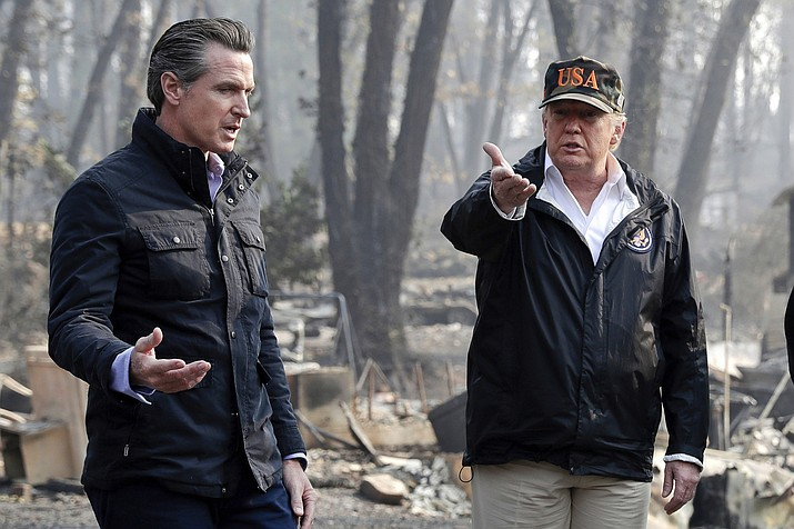 President Donald Trump talks with then California Gov.-elect Gavin Newsom, left, during a visit to a neighborhood impacted by the wildfires in Paradise, Calif. Nearly two years ago President Trump ordered the U.S. Forest Service and the Department of Interior to make federal lands less susceptible to catastrophic wildfires. But the agencies fell short of his goals in 2019, treating a combined 4.3 million acres — just over half of the 8.45 million acres the president sought. It was only slightly better than their average annual performance over nearly two decades, according to government data. (AP Photo/Evan Vucci, File)