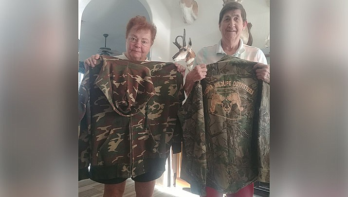 Page McDonald, left, and Jennifer Chambers pose with some of the hunting gear that Chambers donated to the Arizona Elk Society's Heroes Rising program. The program provides clothing and other outdoors gear for disabled veterans. (Photo by Don Martin/For the Miner)