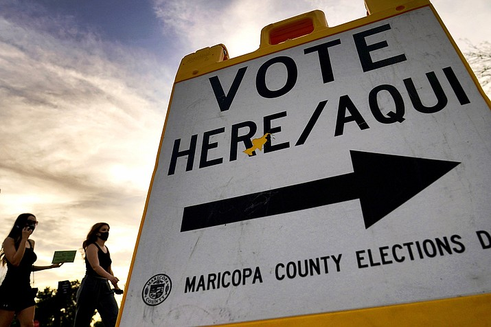 Voters deliver their ballot to a polling station, Nov. 3, 2020, in Tempe, Arizona. (AP Photo/Matt York)