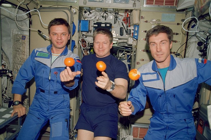 In this photo provided by NASA, the Expedition 1 crew members pose with fresh oranges onboard the Zvezda Service Module of the Earth-orbiting International Space Station on Dec. 4, 2000. Pictured, from left, are cosmonaut Yuri P. Gidzenko, Soyuz commander; astronaut Bill Shepherd, mission commander; and cosmonaut Sergei K. Krikalev, flight engineer. (NASA via AP)