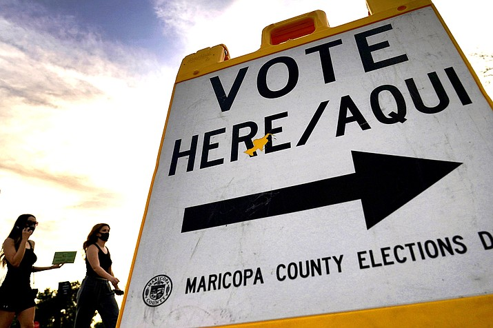 Voters deliver their ballot to a polling station, Tuesday, Nov. 3, 2020, in Tempe, Ariz. (AP Photo/Matt York)
