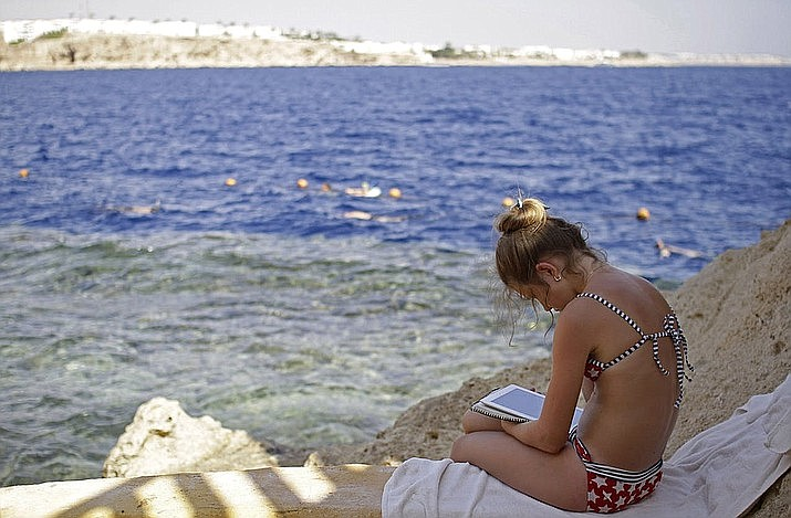 In this 2015 file photo, a Russian tourist sits by the water in the resort city of Sharm el-Sheikh, south Sinai, Egypt. A young Ukrainian tourist lost an arm and an Egyptian tour guide a leg in a rare shark attack at the end of October off Egypt's Red Sea resort of Sharm El-Sheikh, officials said last Tuesday. (Ahmed Abd El-Latif/Asoociated Press. file)