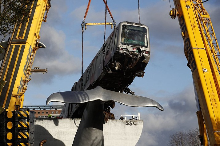 A salvaging crew uses a crane to lift a metro train carriage off of the whale's tail of a sculpture after it rammed through the end of an elevated section of rails with the driver escaping injuries in Spijkenisse, near Rotterdam, Netherlands, Tuesday, Nov. 3, 2020. (AP Photo/Peter Dejong)