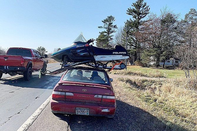 This undated photo provided by The Wisconsin Department of Transportation shows a snowmobile strapped to the roof of a Toyota Corolla in Northwestern Wisconsin Sunday Nov. 1, 2020. The Wisconsin State Patrol pulled over the driver on Highway 63 in northwestern Wisconsin Sunday afternoon after seeing the snowmobile perched sideways on top of the sedan. (Wisconsin Department of Transportation via AP)
