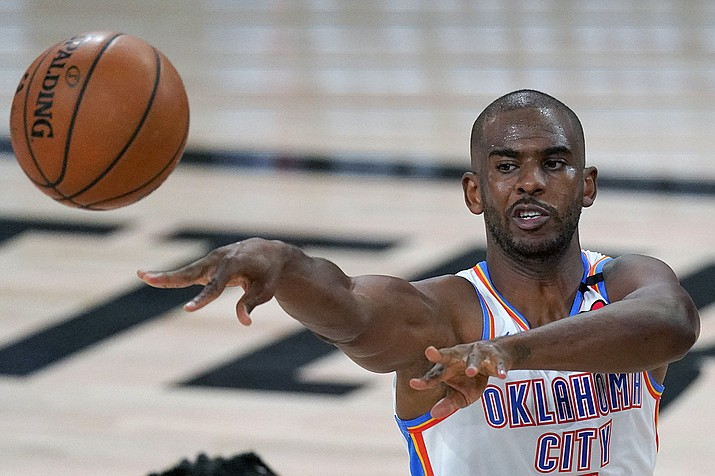 Oklahoma City Thunder's Chris Paul (3) makes a pass during the first half of an NBA first-round playoff basketball game against the Houston Rockets in Lake Buena Vista, Fla., in this Wednesday, Sept. 2, 2020, file photo. A person with knowledge of the situation says All-Star guard Chris Paul is being traded from the Oklahoma City Thunder to the Phoenix Suns, where he'll play alongside one of the league's most dynamic young scorers in fellow All-Star Devin Booker. The Thunder are acquiring Ricky Rubio, Kelly Oubre, Jalen Lecque, Ty Jerome and a first-round pick that will be conveyed sometime between 2022 and 2025, said the person who spoke to The Associated Press on condition of anonymity because the trade had not been finalized by the league. (Mark J. Terrill, AP File)