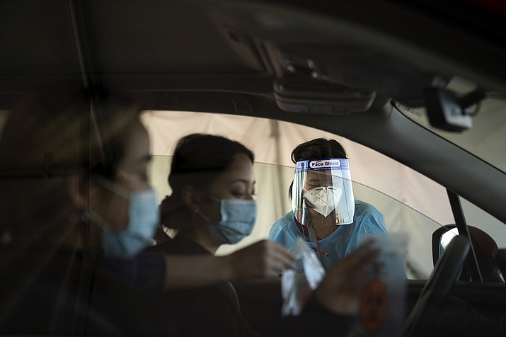 Medical assistant Linh Nguyen assists two women with COVID-19 testing at a testing site set up at the OC Fairgrounds in Costa Mesa, Calif., Monday, Nov. 16, 2020. (Jae C. Hong/AP)