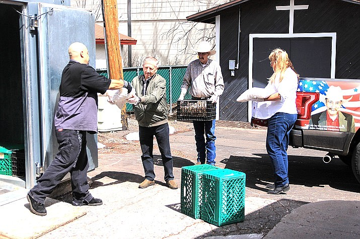 Williams Senior Center employees Cisco Parades (left) and Darlene Foster (right) collect donated food from Williams City Councilman Bernie Hiemenz and Williams Mayor John Moore in March. The city is working toward taking over management of the senior center, which is currently overseen by Coconino County. (Wendy Howell/WGCN)