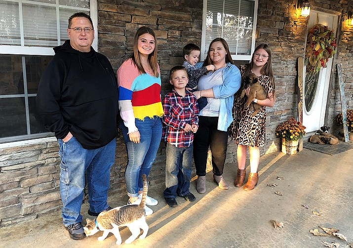 Keith Michael, left, poses with his children, from left, Jessica, Hunter, Houston, Sara and Holly, outside their home on Friday, Nov. 13, 2020, in Jonesboro, Ark. Among the victims of the coronavirus is Michael's wife, fourth-grade Arkansas teacher Susanne Michael, who died less than three months after celebrating the adoption of three of the children. (Adrian Sainz/AP)