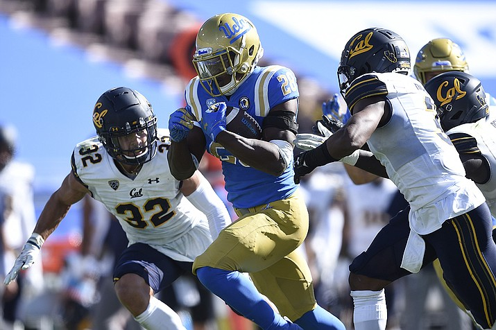 UCLA running back Brittain Brown, center, runs the ball for a touchdown past California safety Daniel Scott, left, and Elijah Hicks during the second half of an NCAA college football game against California in Los Angeles, Sunday, Nov. 15, 2020. UCLA won 34-10. (Kelvin Kuo/AP)