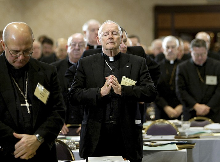In this Nov. 10, 2003 file photo, Cardinal Theodore Edgar McCarrick, Archbishop of Washington, D.C., center, joins fellow clergy in prayer at the end of the opening session of the U.S. Conference of Catholic Bishops meeting in Washington. McCarrick – who was defrocked by Pope Francis in 2019 – served as head of Catholic dioceses in Metuchen and Newark, New Jersey, and in Washington. A report released by the Vatican on Monday, Nov. 9, 2020, found that three decades of bishops, cardinals and popes dismissed or downplayed reports of McCarrick's misconduct with young men. (J. Scott Applewhite/AP, file)