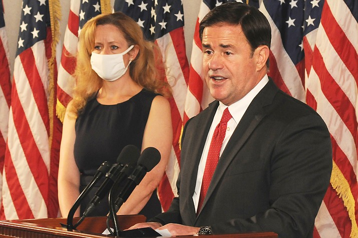 Gov. Doug Ducey explains why he's not implementing new restrictions even as he concedes Wednesday  that the rate of COVID-19 infection in Arizona is on the rise. With him is state health chief Cara Christ. (Capitol Media Services photo by Howard Fischer)