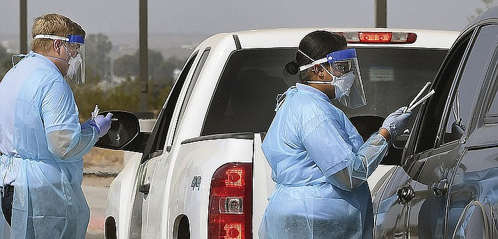 In this Oct. 17, 2020, file photo, Arizona Western College EMT Academy students Natus Humphrey, left, and Shayla Watson explain the procedure and hand out kits to participants in a drive-thru COVID-19 saliva test on the main campus at the school in Yuma, Ariz. Arizona on Thursday, Nov. 19, 2020, reported over 4,000 additional known COVID-19 cases, the most in a single day since July. The Department of Health Services also reported 19 additional deaths due to the coronavirus. (Randy Hoeft/The Yuma Sun via AP, File)