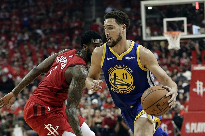 In this May 10, 2019, file photo, Golden State Warriors' Klay Thompson (11) drives past Houston Rockets' Iman Shumpert during the first half of Game 6 of a second-round NBA basketball playoff series in Houston. The Warriors said Thursday, Nov. 19, 2020, that Thompson has suffered a torn right Achilles tendon and is expected to miss the upcoming season. Thompson was injured during a pickup game in Southern California the day before. (Eric Gay, AP File)