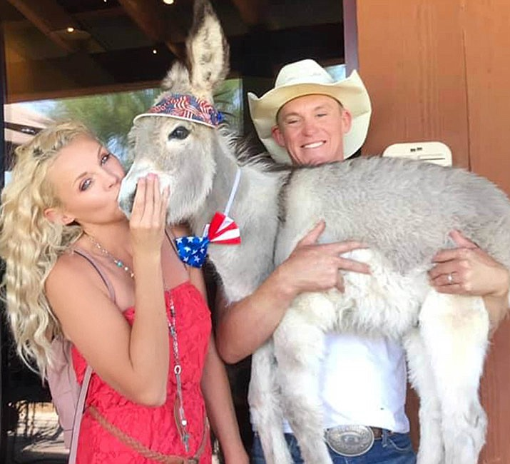 "Walter, the orphaned donkey and mayor of Oatman, is shown with his family, Brad and Kelly Blake, left. Above is the cover of ""Walter Finds a Home,"" the first in a series of children's books about the burro. (Courtesy photos)"
