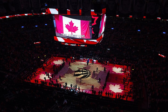 In this April 16, 2019, file photo, fans sing the Canadian national anthem before Game 2 of an NBA basketball first-round playoff series between the Orlando Magic and the Toronto Raptors in Toronto. The Canadian government has denied a request by the NBA and the Raptors to play in Toronto amid the pandemic. An official familiar with the federal government's decision told The Associated Press on Friday, Nov. 20, 2020, there is too much COVID-19 circulating in the United States to allow for cross-border travel that is not essential. (Nathan Denette/The Canadian Press via AP, File)
