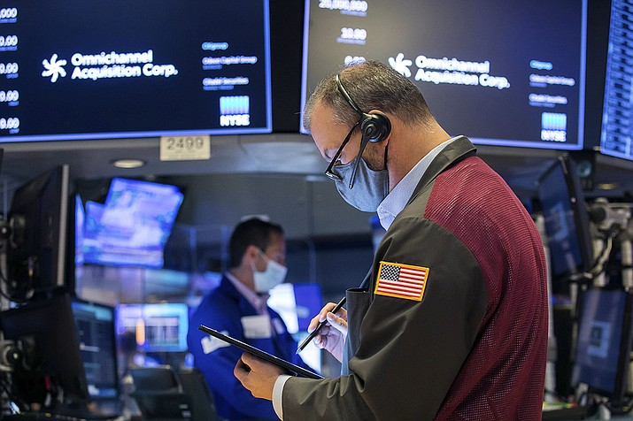 In this photo provided by the New York Stock Exchange, a trader works on the floor during the IPO of Omnichannel Acquisition Corporation, Friday, Nov. 20, 2020. U.S. stocks are pulling a bit lower in midday trading Friday as worries about the worsening pandemic weigh on rising optimism about a coming coronavirus vaccine. (Courtney Crow/New York Stock Exchange via AP)