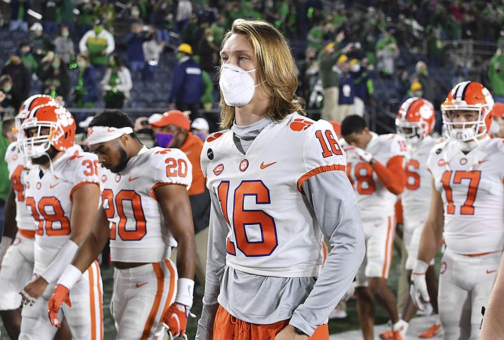In this Saturday, Nov. 7, 2020 photo, Clemson quarterback Trevor Lawrence (16) leaves the field with his teammates after Clemson lost to Notre Dame 47-40 in two overtimes during an NCAA college football game. As virus disruptions mount and the Dec. 19 end of college football's regular season draws closer, the possibility grows that conference championships, major awards and even College Football Playoff participants will be determined by COVID-19. (Matt Cashore/Pool Photo via AP, File)