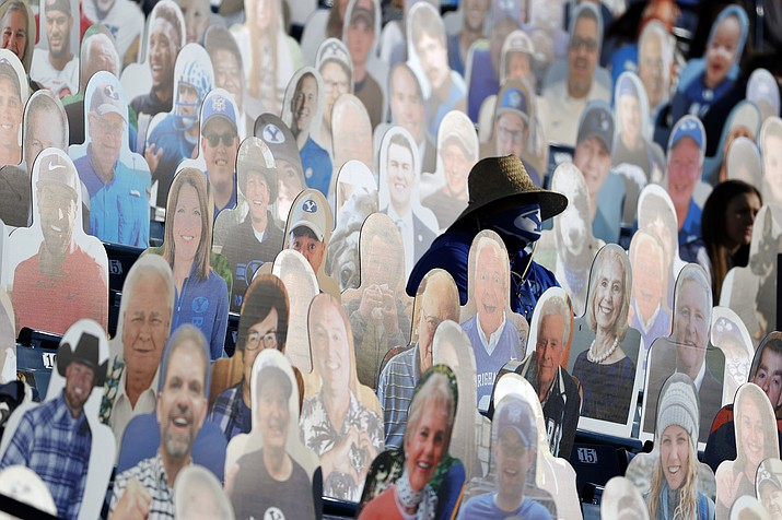 A BYU fans sits among the cardboard fan cutouts during an NCAA college football game against North Alabama, Saturday, Nov. 21, 2020, in Provo, Utah. (Jeff Swinger, Pool/AP)