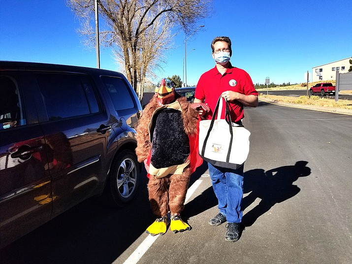 """Tom Turkey"" and Daniel Hendrix greet incoming recipients for a Thanksgiving meal distribution Nov. 19. (Lo Frisby/WGCN)"