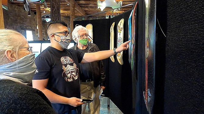 Hopi/Tewa Contemporary Artist Duane Koyawena discusses his skateboard art with museum members Dean and Lori Mickelson at the Museum of Indigenous People Guest Artist Series in Prescott Nov. 13. (Jesse Bertel/Courier)