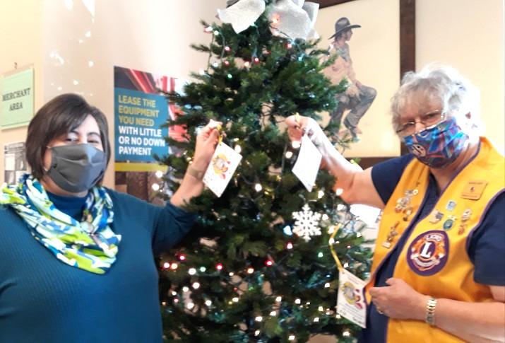 National Bank of Arizona Manager Tanya Christie and Toys for Kids Chairperson Bonnie Dent place tags on a tree at the National Bank of Arizona. (Submitted photo)
