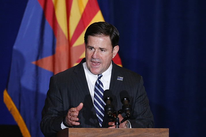 """In this file photo, Arizona Gov. Doug Ducey speaks at an event in Mesa. The governor said earlier this week that Arizona could be """"back to normal'' by this summer once Arizonans get vaccinated for COVID-19.  (Ross D. Franklin/AP file)"""