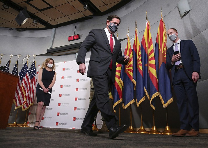 """Ariz. Gov. Doug Ducey walks out after addressing the media on COVID-19 during a news conference in Phoenix on Wednesday, Nov. 18, 2020. Behind him is Dr. Cara Christ. Health officials are begging people not to travel for Thanksgiving and asking families to resist inviting anyone over to the house who does not already live there. """"Don't let down your guard, even around close friends and relatives who aren't members of your household,"""" Arizona's health department said on Twitter.(Michael Chow/The Arizona Republic via AP)"""
