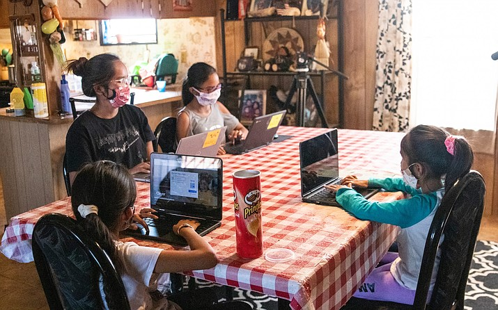 The Begaye sisters do their schoolwork at their home in Blue Gap, Arizona Sept. 24. From left: High school senior Chenoa, fourth-grader Sonora, first-grader Annabah and second-grader Winona. On the Navajo Nation, some students must drive for miles to access Wi-Fi hotspot for schoolwork. (Megan Marples/Cronkite News)