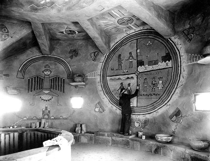 Hopi artist Fred Kabotie stands on a stone bench and colors in figures within a painted circle mural at the Desert View Watchtower circa 1930. (Photo/NPS)