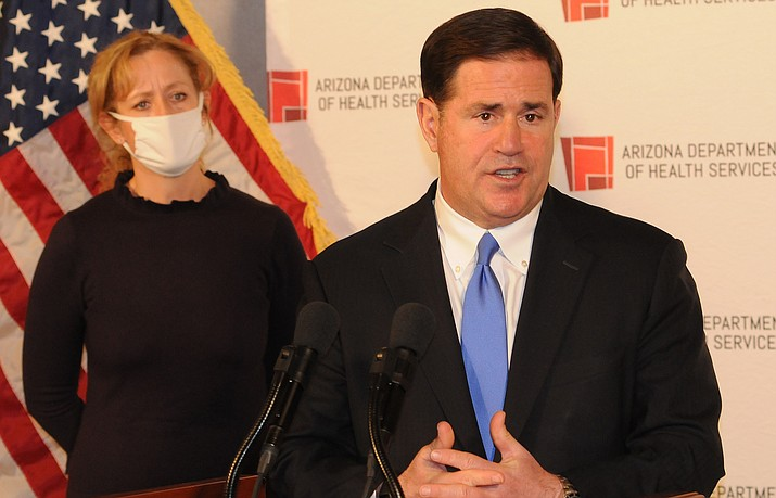 Gov. Doug Ducey explains Wednesday why he won't impose additional restrictions even as the state is setting new records for COVID-19 infections. With him is state Health Director Cara Christ. (Capitol Media Services photo by Howard Fischer)