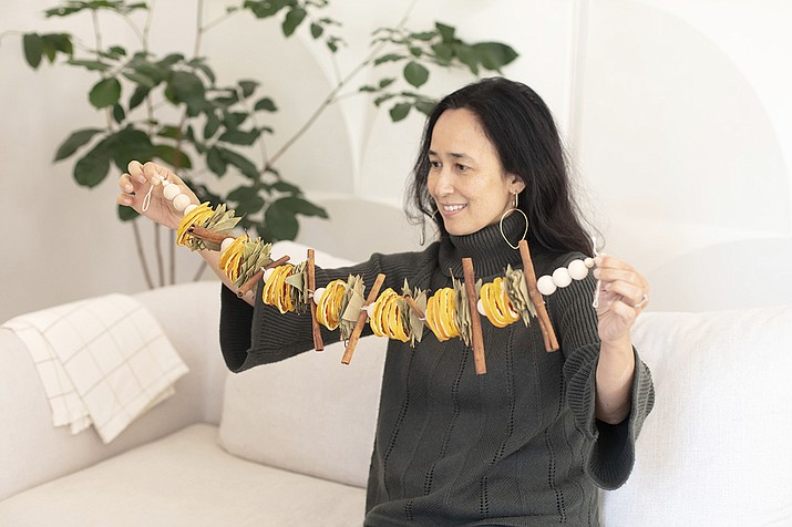 """San Francisco Bay-area based Mariam Naficy, shown here, founder of online design marketplace Minted, has been making garlands this year out of various materials, including fragrant dried orange slices. """"What I love about these is that they're stunning yet easy to make. You can display on a mantle, bookcase, or drape one on your dining table surrounded by tea candles for a simple, aromatic centerpiece."""" (Minted via AP)"""