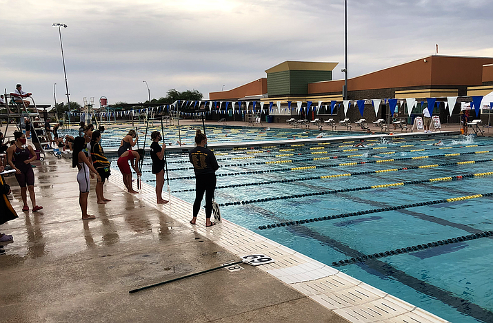 During their events, swimmers adjust to new COVID-19 protocols, including wearing face masks while waiting outside of the pool. (Photo by Edwin Perez/Cronkite News)