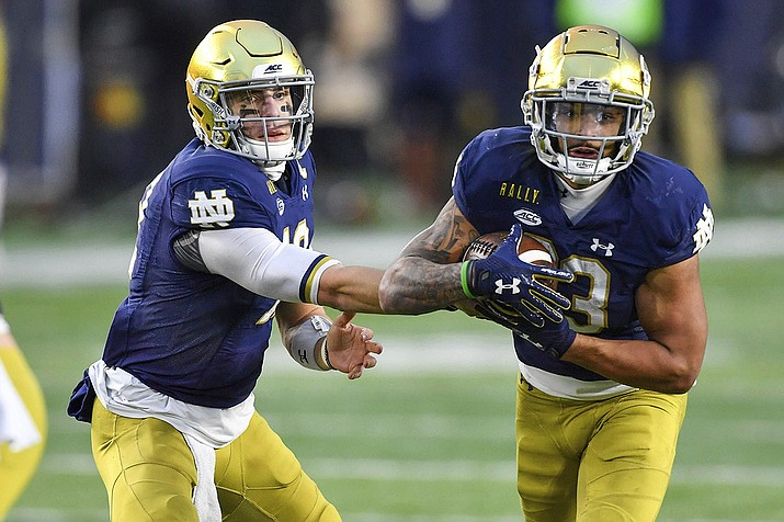 Notre Dame quarterback Ian Book (12) hands off to running back Kyren Williams (23) during the third quartero of the team's NCAA college football game against Syracuse on Saturday, Dec. 5, 2020, in South Bend, Ind. (Matt Cashore/Pool Photo via AP)