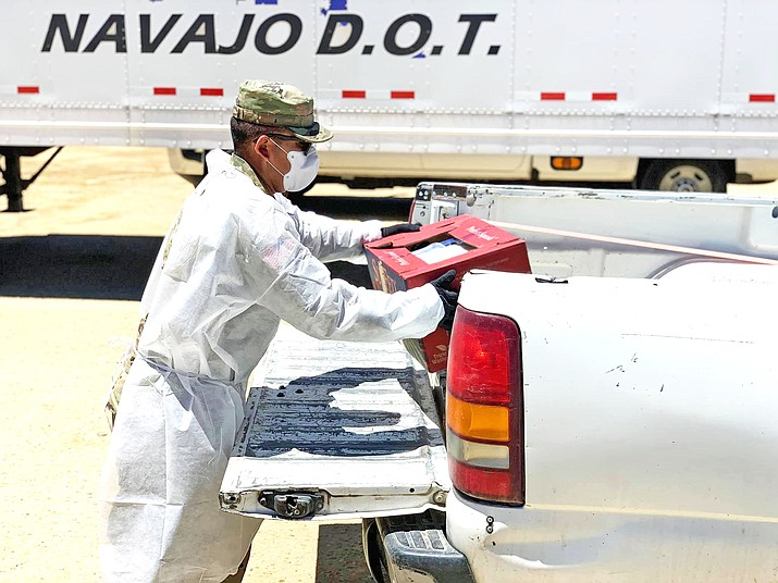 A National Guard member helps load COVID-19 relief boxes into a vehicle on the Navajo reservation in June. The Nation is reporting a dramatic increase in coronavirus cases.  (Photo/Navajo Nation)