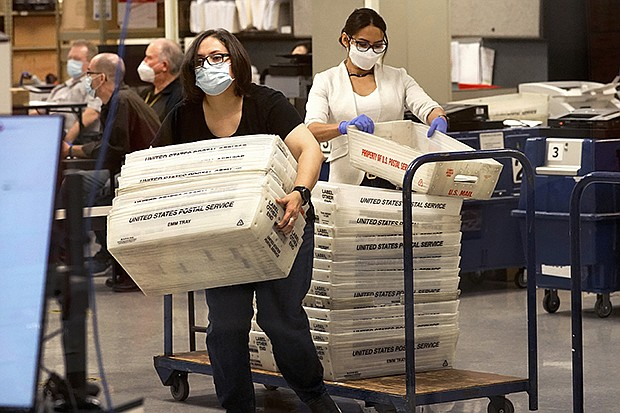 Arizona elections officials carry ballots in trays to be counted inside the Maricopa County Recorder's Office, Friday, Nov. 6, 2020, in Phoenix. A federal judge late Wednesday tossed the last of the legal challenges to the decision by Arizona voters to choose Joe Biden for president. (AP Photo/Matt York, file)