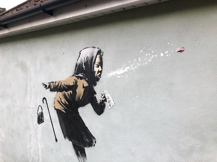 """Banksy's latest mural titled """"Aachoo!!"""" that has appeared on a wall in Bristol, England, Thursday Dec. 10, 2020. Banksy's latest mural has delayed - but not thwarted - a homeowner's plans to sell in Bristol after it recently appeared on the house's exterior wall. (Claire Hayhurst/PA via AP)"""