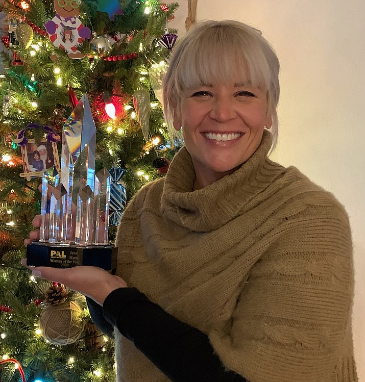 Jessi Hans holds up her PAL Woman of the Year Award in front of her family Christmas tree. (Prescott Area Leadership/Courtesy)