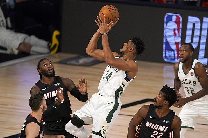 Miami Heat's Goran Dragic, bottom left, Jae Crowder, top left, and Jimmy Butler (22) defend as Milwaukee Bucks' Giannis Antetokounmpo (34) shoots during the first half of an NBA basketball conference semifinal playoff game inin Lake Buena Vista, Fla., in this Monday, Aug. 31, 2020, file photo. Bucks Khris Middleton, right rear, looks on. Having the NBA's best regular-season record and the league's MVP each of the last two years hasn't paid off for the Bucks in the playoffs. They're hoping an offseason overhaul of their roster will help them earn the title that has eluded this franchise since 1971 and make sure two-time reigning MVP Giannis Antetokounmpo stays in Milwaukee for years to come.(Mark J. Terrill, AP File)