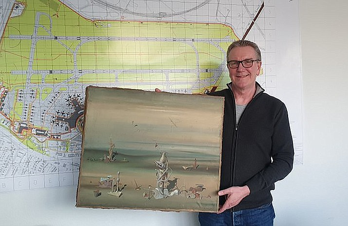 In this photo released by the police department in Duesseldorf on Thursday Dec. 10, 2020, showing Chief Detective Michael Dietz holding a painting from French artist Yves Tanguy. A businessman, whose identity was not given, boarded a flight from Duesseldorf to Tel Aviv on Nov. 27, but forgot the painting by French surrealist Yves Tanguy, which was wrapped in cardboard, on the check-in counter (Polizei Duesseldorf via AP)