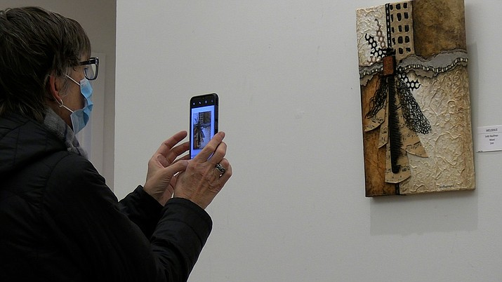 A patron at 'Tis Art Gallery in Prescott takes a photo of one of the paintings at the 4th Friday Art Walk on Friday, Nov. 27, 2020. (Jesse Bertel/Courier)