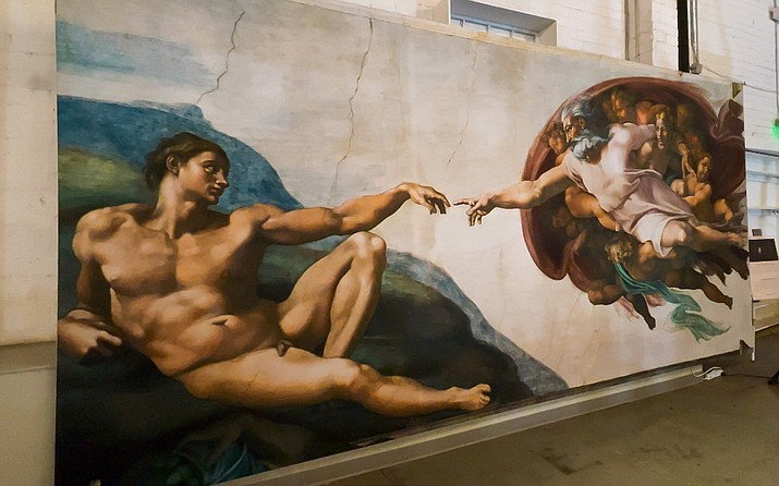 """""""Michelangelo's Sistine Chapel: The Exhibition"""" showcases life-size prints of the famous frescoes found inside the Vatican. The traveling exhibit is showing in Phoenix through Feb. 14. One of the more iconic paintings on display is """"The Creation of Adam."""" (Megan Marples/Cronkite News)"""