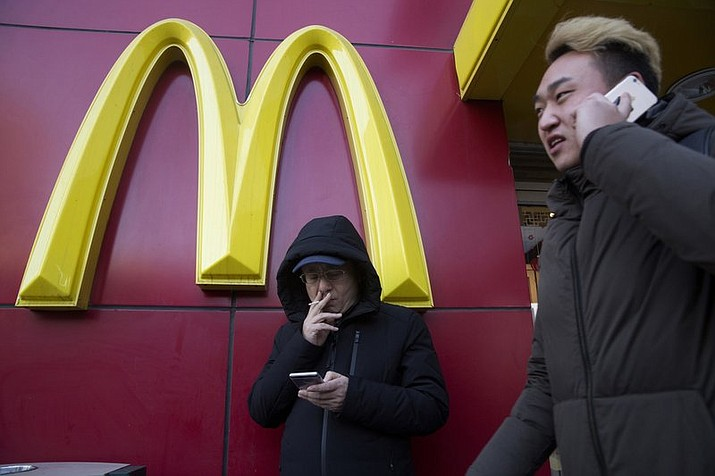 In this Jan. 10, 2017, file photo, a man smokes outside a McDonald's restaurant in Beijing, China. McDonald's is selling a sandwich made of Spam topped with crushed Oreo cookies Monday, Dec. 21, 2020 in China in an attention-grabbing move that has raised eyebrows. (AP Photo/Ng Han Guan, File)
