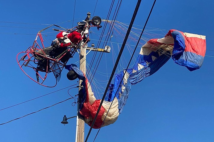 In this photo provided by the California Highway Patrol, a man dressed as Santa Claus who was flying on a powered parachute on his way to deliver candy canes to children is seen stuck on power lines in Rio Linda, Calif., on Sunday, Dec. 20, 2020. The man was rescued uninjured. The incident happened shortly after the man took off near a school in Rio Linda and then hit and became suspended in power lines, a Federal Aviation Administration spokesman told KCRA-TV. (California Highway Patrol via AP)