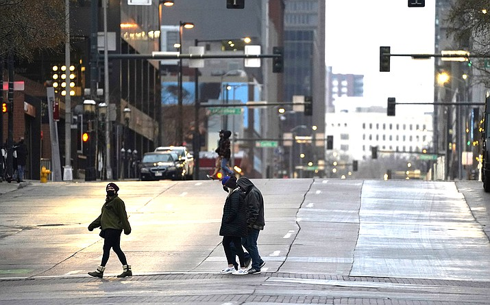 Pedestrians wear masks while crossing an empty road at the intersection of Market Street and 15th Avenue during the evening rush hour Dec. 28, 2020, in downtown Denver. (AP Photo/David Zalubowski)