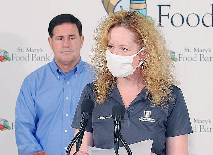 State Health Director Cara Christ, shown here at an October news conference with Gov. Doug Ducey behind her, acknowledged Wednesday that only about 18% of the more than 314,000 doses received by this week actually have ended up in the arms of Arizonans. (Capitol Media Services file photo by Howard Fischer)
