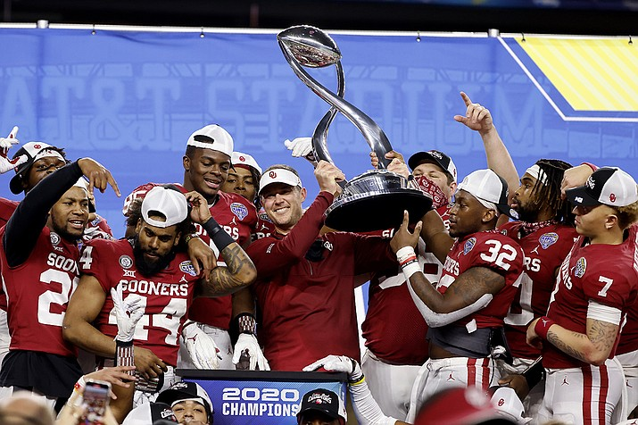 Oklahoma coach Lincoln Riley stands surrounded by the team as he holds up the trophy following Oklahoma's 55-20 win over Florida in the Cotton Bowl NCAA college football game in Arlington, Texas, Wednesday, Dec. 30, 2020. (Michael Ainsworth/AP)