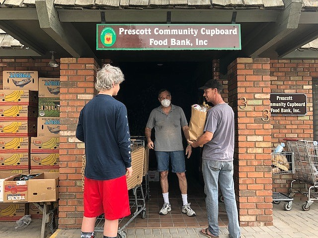 Volunteer Bruce Dovala distributes food bags on one of the weekday distributions. (Prescott Community Cupboard/Courtesy)
