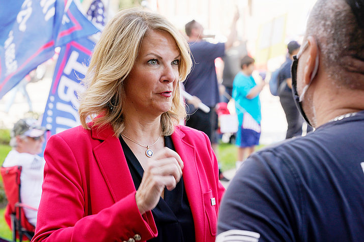 In this file photo Dr. Kelli Ward, left, chair of the Arizona Republican Party, talks with a supporter of President Donald Trump as they join the crowd at a rally outside the Arizona state capitol Nov. 7, 2020, in Phoenix. It took just eight hours and three minutes for the Fifth Circuit Court of Appeals from the time Kelli Ward and her fellow plaintiffs filed their paperwork for the judges to rule they have no legal standing to challenge the Electoral Count Act.  (Ross D. Franklin/AP, file)